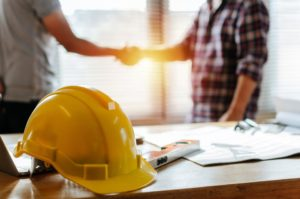 construction hat on table and people shaking hands
